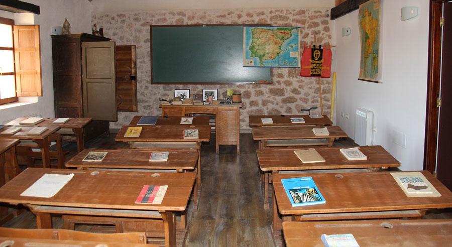 Clase antigua con mesas de madera y pizarra